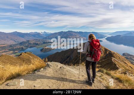Femme debout au point de vue de Roys Peak, regardant le mont aspirant, lac Wanaka, île du Sud, Nouvelle-Zélande Banque D'Images