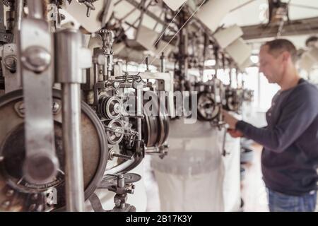 Vue floue de l'homme travaillant dans une usine de textile Banque D'Images
