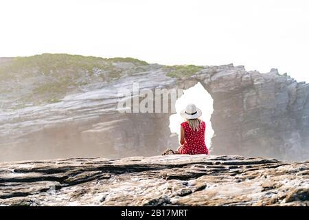 Blonde femme portant une robe rouge et chapeau assis sur le rocher et regardant Natural Arch à Playa de Las Catedrales, Espagne Banque D'Images