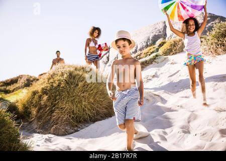 Famille marchant à travers les dunes à la plage Banque D'Images