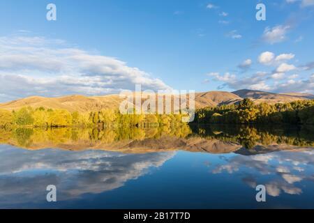 Nouvelle-Zélande, Franklin District, Glenbrook, collines boisées reflétant dans le lac Wairepo Arm en automne