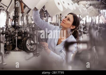 Femme vérifiant le rouleau de coton dans une usine de textile Banque D'Images