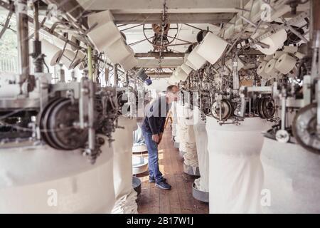 Homme travaillant dans une machine dans une usine textile Banque D'Images