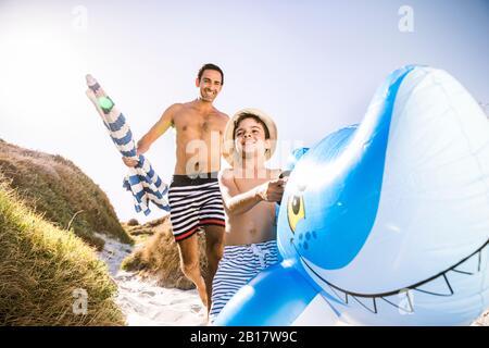 Père et fils avec requin gonflable marchant à travers les dunes à la plage Banque D'Images