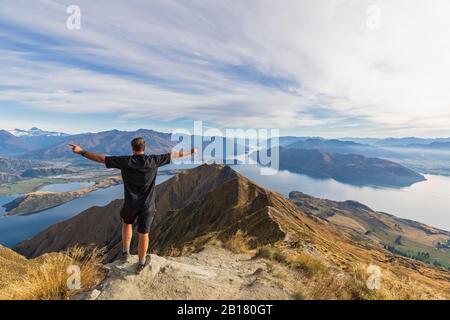 Randonneur debout au point de vue de Roys Peak, regardant le mont aspirant, le lac Wanaka, l'île du Sud, la Nouvelle-Zélande