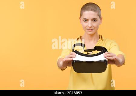 Jeune femme dans ses 30 ans utilisant des lunettes de réalité virtuelle. Femme portant des lunettes VR isolées sur fond jaune. Concept VR Experience. Banque D'Images