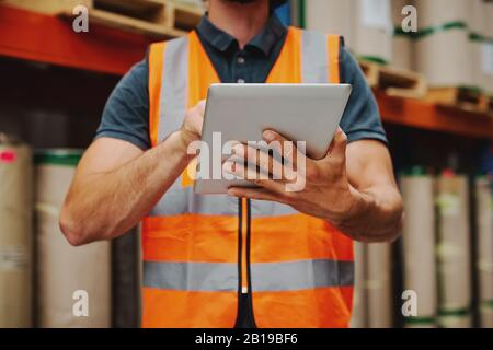 Gros plan du travailleur de l'entrepôt dans la veste orange qui maintient la tablette numérique en état de marche tout en vérifiant l'inventaire et la commande