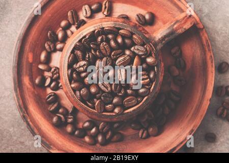 Grains de café torréfiés secs dans un bol en céramique, à proximité. Vue de dessus