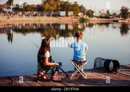 Deux jeunes petits amis mignons, un garçon et une fille pêchant sur un lac lors d'une journée d'été ensoleillée. Les enfants jouent. Amitié. Banque D'Images