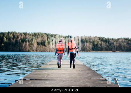 frère et sœur marchant le long d'un quai en hiver avec des gilets de sauvetage