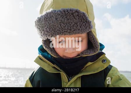 portrait d'un jeune garçon enveloppé chaud à la plage en hiver