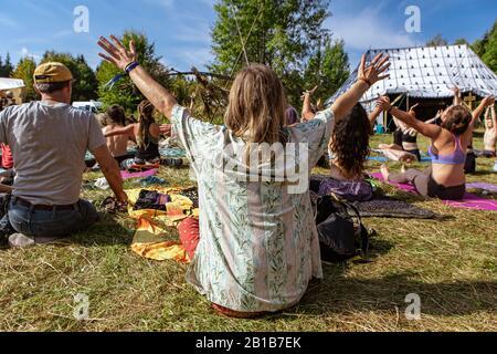 Vue rapprochée et arrière d'un homme avec de longs cheveux blonds et des bras levés, prenant part à la méditation de groupe lors d'un festival célébrant les cultures traditionnelles Banque D'Images