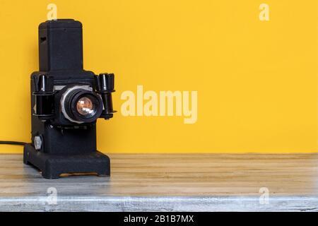 Projecteur vintage. Gros plan d'un ancien projecteur noir en cours d'exécution pour regarder des diapositives et des bandes filmstries sur une table en bois sur fond jaune. Les Animateurs Banque D'Images