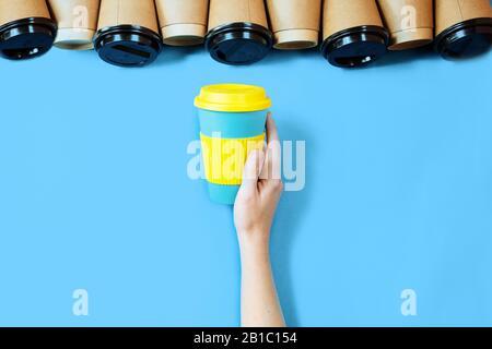 Tasses à café en bambou fond bleu.Une tasse à café ECO dans la main femelle. Banque D'Images