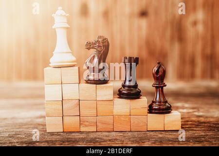 Pièces de chés sur un bâtiment d'escalier avec des blocs de bois, hiérarchie métaphore, classement, travail d'équipe et stratégie dans le concept d'affaires