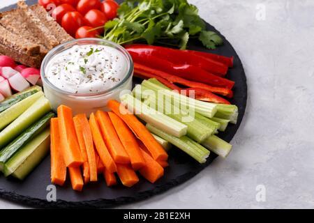 En-cas de légumes sains avec sauce au yaourt sur une planche ronde en pierre d'ardoise, vue de dessus rapprochée, espace de copie