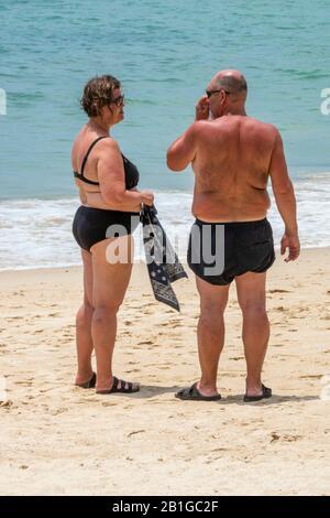 un couple d'âge moyen se tenant sur une plage de patong, thaïlande, bronzer sur la plage de sable au bord de la mer.