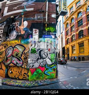 Peinture du crâne et divers dessins peints, la chaussée couverte de graffitis avec la famille qui descend la rue en arrière-plan. Hosier Street, Melbourne Lan Banque D'Images