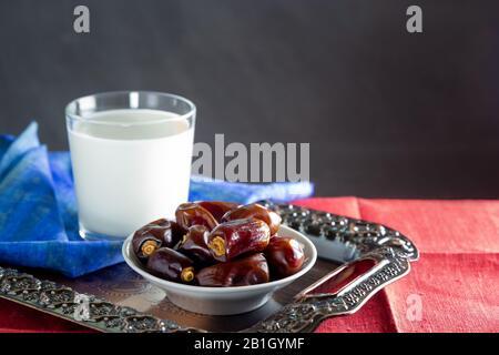 Dattes et un verre de lait sur plateau en métal et serviettes colorées. Ramadan, Iftar concept alimentaire. Arrière-plan sombre, espace de copie Banque D'Images