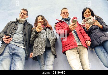 Groupe de jeunes amis regardant leurs smartphones dans le vieux centre-ville - Tecnologie et concept de réseau social - Filtre Chaud Banque D'Images