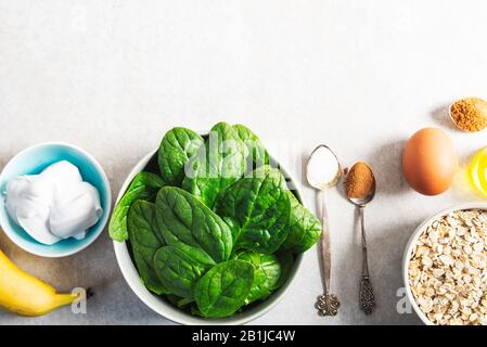 Ingrédients pour des crêpes vertes saines comme les épinards, le lait de coco, la banane, l'oeuf et l'avoine. Petit-déjeuner végétarien et sans gluten Banque D'Images