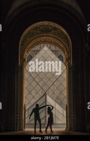 Dansant couple silhouette au Louvre Paris avec les pyramides derrière eux le couple danse dans l'arche Banque D'Images