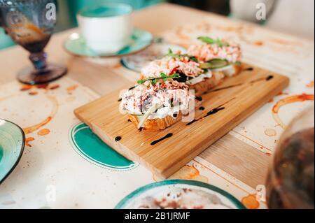 Très belle et délicieuse bruschetta avec de la viande de crabe et de l'avocat sur une plaque en bois et décorée avec de la sauce. Un petit déjeuner sain et attrayant dans un soupir Banque D'Images