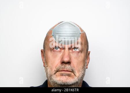 un homme qui protège son cerveau de la panique avec un masque Banque D'Images
