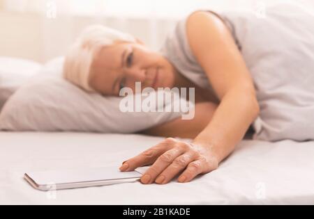 Femme senior fatiguée au lit, heure de vérification sur son téléphone
