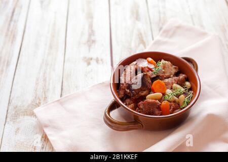 Cassoulet. Contenant des saucisses de porc à la viande, des oies, des canards et parfois des mutons et deux types de haricots blancs. Cuisine française. Sur le vieux dos blanc en bois Banque D'Images