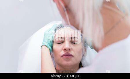 Le jeune médecin esthéticien se préparant à faire l'injection dans le front femelle. Le médecin cosmologiste effectue un traitement anti-âge et le lève-visage surveillé