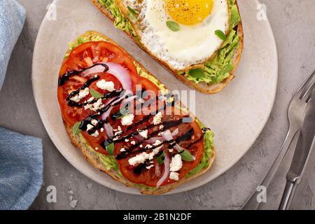 Toasts avocat avec œufs frits et tomates à l'ancienne Banque D'Images