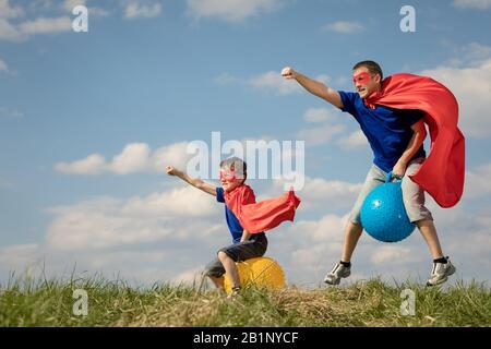 Père et fils jouer au super-héros de la journée. Les gens s'amuser en plein air.Ils sauter sur des ballons gonflables sur la pelouse. Concept de famille accueillante. Banque D'Images