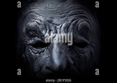 Figure effrayante avec masque dans le noir, macro shot