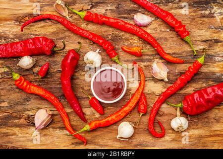 Sauce thaïlandaise traditionnelle Sriracha avec ingrédients. Piment rouge et orange légèrement séché, ail. Dans un bol en céramique, arrière-plan en écorce de bois, vue de dessus Banque D'Images