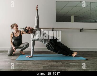Une entraîneuse personnelle féminine entraîne un client masculin en train de faire une planche latérale Banque D'Images