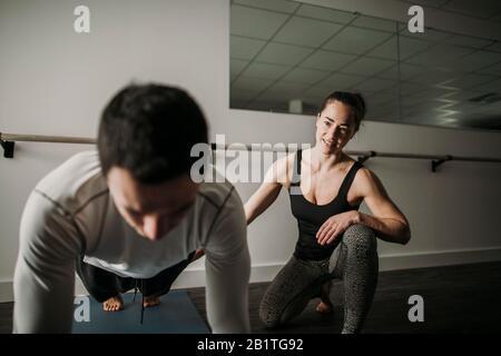 une entraîneuse personnelle féminine encadre un client masculin en train de faire des retouches Banque D'Images