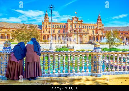 Deux religieuses se penchent sur les mains courantes en céramique du canal sous l'ombre des arbres et observent l'activité des gens sur la Plaza de Espana, Séville, Espagne Banque D'Images