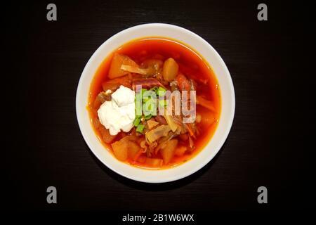 Soupe Borscht dans un bol blanc sur fond en bois sombre. Vue de dessus. Célèbre soupe traditionnelle de borshch ukrainien et russe avec betterave et chou. Rouge Banque D'Images