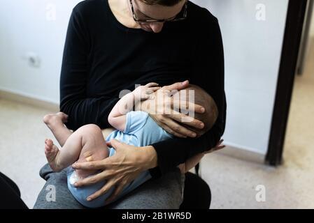 Bébé qui pleure après la vaccination avec l'aide de bande ou le plâtre dans la cuisse, réconforté par sa mère qui allaite lui. Banque D'Images