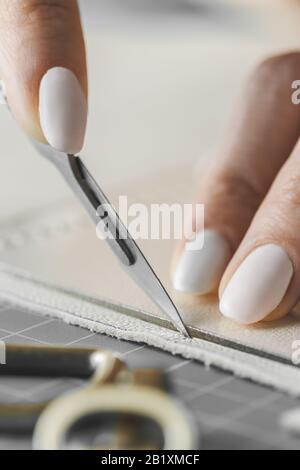 Femme concepteur de sac à main mesurant le cuir et découpant les détails dans un atelier studio Banque D'Images