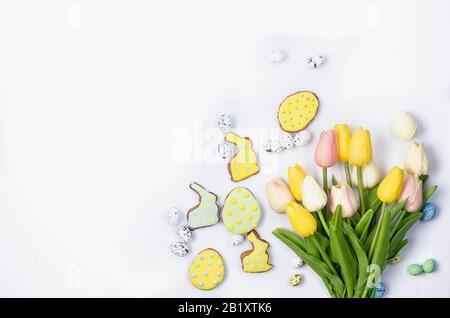 Biscuits maison de Pâques au pain d'épices avec givrage, œufs décorés et tulipes sur un fond blanc / Concept De Joyeuses pâques. Espace de copie, plat, modèle Banque D'Images