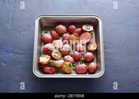Raifort rôti dans la plaque de cuisson sur fond de pierre bleue. Cuisine végétalienne végétarienne. Vue rapprochée