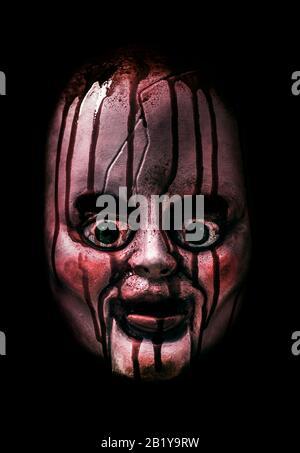 Tête de poupée créepy sanglante dans le noir