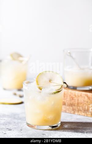 Un petit verre de mocktail ou de cocktail rafraîchissant à base de soda de poire sur fond de béton gris. Boisson estivale sans alcool. Mise au point sélective