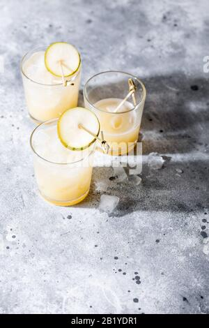 Un petit verre de mocktail ou de cocktail rafraîchissant à base de soda de poire sur fond gris en béton avec ombre. Boisson estivale sans alcool