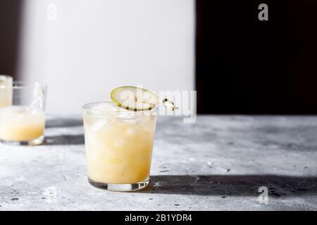 Un petit verre de mocktail ou de cocktail rafraîchissant à base de soda de poire sur fond de béton gris. Boisson estivale sans alcool. Orientation horizontale