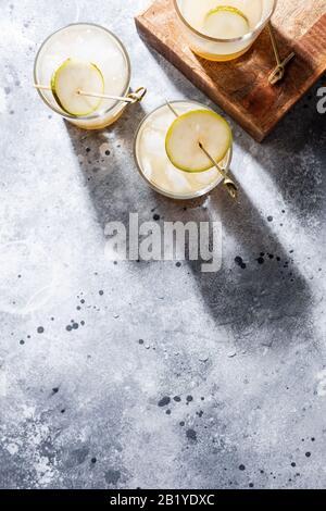Un petit verre de mocktail ou de cocktail rafraîchissant à base de soda de poire sur fond de béton gris. Boisson estivale sans alcool. Orientation verticale