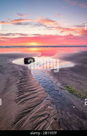 Coucher de soleil romantique et spectaculaire sur le nord du Devon, plage, côte, littoral, vie costale, magnifique, littoral, rochers, réflexions, galets, nuages, Royaume-Uni Banque D'Images