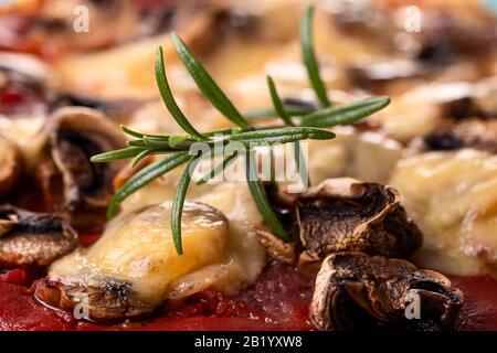romarin sur une pizza aux champignons sur une plaque Banque D'Images